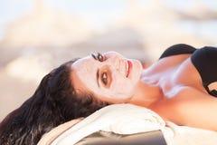 Vrouw in Kuuroordsalon De mooie vrouw krijgt kuuroordmasker op het zonnige strand in kuuroord Stock Afbeelding