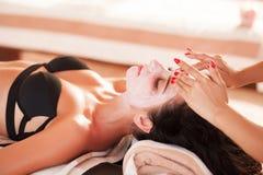 Vrouw in Kuuroordsalon De mooie vrouw krijgt kuuroordmasker op het zonnige strand in kuuroord Stock Fotografie