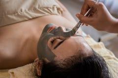 Vrouw in kuuroordsalon die gezichtsmasker door schoonheidsspecialist krijgen stock fotografie