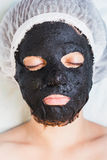 Vrouw in kuuroordsalon met het zwarte masker van het moddergezicht Royalty-vrije Stock Afbeeldingen