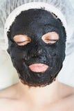 Vrouw in kuuroordsalon met het zwarte masker van het moddergezicht Royalty-vrije Stock Foto