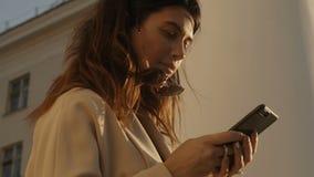 Vrouw in laag die smartphone gebruiken stock videobeelden