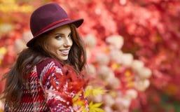 Vrouw in laag met hoed en sjaal in de herfstpark Royalty-vrije Stock Foto's