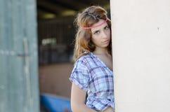 Vrouw in landbouwbedrijf met krullend haar, die tegen de muur leunen stock afbeeldingen