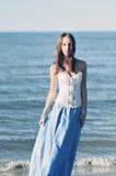 Vrouw in lange kleding aan de overzeese kant. Stock Afbeeldingen
