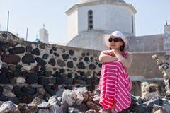 Vrouw in lange kledingszitting op de stenen dichtbij de Kerk Stock Fotografie