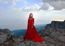 Vrouw in lange rode kleding op de rand van een klip in de bergen Piek van berg ai-Petri stock foto