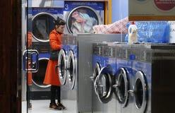 Vrouw in laundromat die op haar kleren wachten Stock Foto