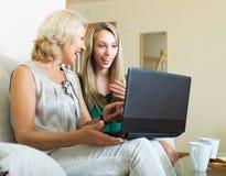Vrouw learnig om laptop van meisje te gebruiken Stock Afbeeldingen