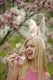 Vrouw of leuk meisje met konijntjesoren bij tot bloei komende magnolia royalty-vrije stock foto's