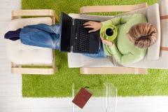 Vrouw in leunstoel met laptop stock fotografie