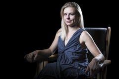 Vrouw in leunstoel op zwarte Royalty-vrije Stock Fotografie