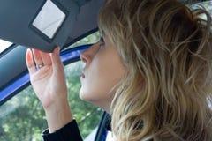Vrouw lookin in autospiegel royalty-vrije stock foto's