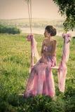 Vrouw in luchtige roze kleding op de schommeling stock afbeeldingen