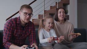 Vrouw, man en zij kind het spelen in videospelletjes en het eten pizz stock video