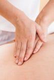Vrouw masseren man terug in kuuroord Stock Afbeeldingen