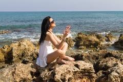 Vrouw mediteren gezet in yogalotusbloem stelt bij het strand Stock Fotografie