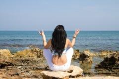 Vrouw mediteren gezet in yogalotusbloem stelt bij het strand Stock Afbeelding
