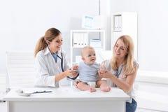 Vrouw met arts van haar baby de bezoekende kinderen stock fotografie