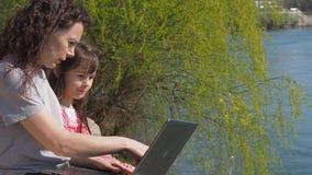 Vrouw met baby en laptop in openlucht Gelukkige familie op de rivierbank De moeder onderwijst een kind op laptop stock footage