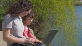 Vrouw met baby en laptop in openlucht Gelukkige familie op de rivierbank De moeder onderwijst een kind op laptop Een de lente zon stock video