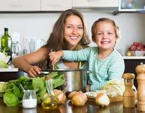 Vrouw met baby het koken bij keuken Royalty-vrije Stock Afbeelding