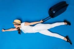 Vrouw met bagage in handenvlieg aan nieuwe reis op blauwe achtergrond Vrouwenvlieg aan nieuwe vliegtuigreis Nieuw avontuur royalty-vrije stock foto's