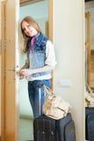 Vrouw met bagage loocking deur Stock Afbeelding