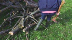 Vrouw met bijl dichtbij brandhout stock footage
