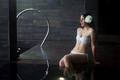 Vrouw met bloem in haarzitting bij het kuuroord Royalty-vrije Stock Foto's