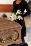 Vrouw met bloemen en doodskist bij begrafenis royalty-vrije stock fotografie