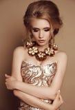 Vrouw met blond haar in elegante gouden kleding en luxueuze halsband stock afbeelding