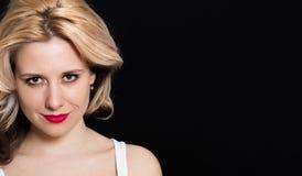 Vrouw met blondekrullen en rode lippenstift op een donkere achtergrond Stock Foto's
