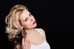 Vrouw met blondekrullen en rode lippenstift op een donkere achtergrond Stock Fotografie