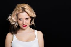 Vrouw met blondekrullen en rode lippenstift op een donkere achtergrond Stock Afbeeldingen