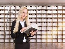 Vrouw met boek in bibliotheek Stock Afbeeldingen