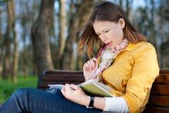 Vrouw met boek in park Stock Afbeelding