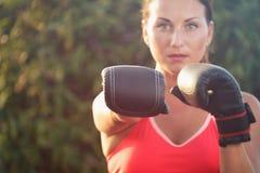 Vrouw met bokshandschoenen over groene achtergrond stock foto