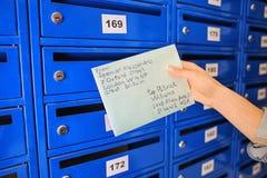 Vrouw met brief dichtbij brievenbus stock foto