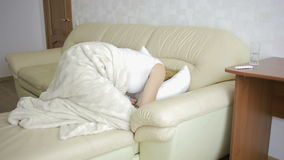 Vrouw met buikpijn die op de bank liggen Meisje het drinken pillenpijnstiller stock videobeelden