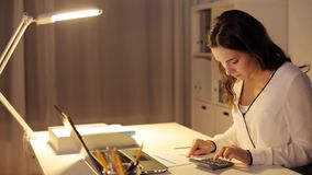 Vrouw met calculator en documenten op nachtkantoor stock video
