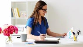 Vrouw met calculator en notitieboekje op kantoor stock footage