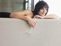 Vrouw met Champagne Glass On Couch Stock Afbeeldingen