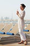 Vrouw met cocktail die zich op het dek van de cruisevoering bevindt Royalty-vrije Stock Afbeeldingen