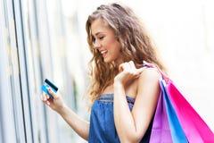 Vrouw met creditcard en het winkelen zakken stock foto's