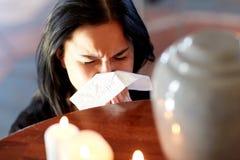 Vrouw met crematieurn bij begrafenis in kerk stock afbeeldingen
