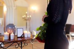 Vrouw met crematieurn bij begrafenis in kerk stock fotografie