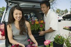 Vrouw met de bloemen van de echtgenootlading in rug van SUV-portret Stock Fotografie