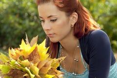 Vrouw met de herfstbladeren Stock Foto