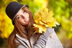 Vrouw met de herfstbladeren Royalty-vrije Stock Afbeeldingen